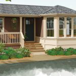 A tan manufactured home with a garden and front porch