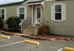 A tan manufactured home with white trim and steps leading to the door