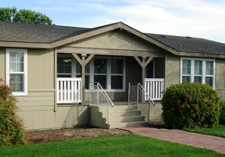 A brown manufactured home with grass out front and steps leading to the door