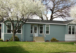A blue manufactured house with trees and a lawn